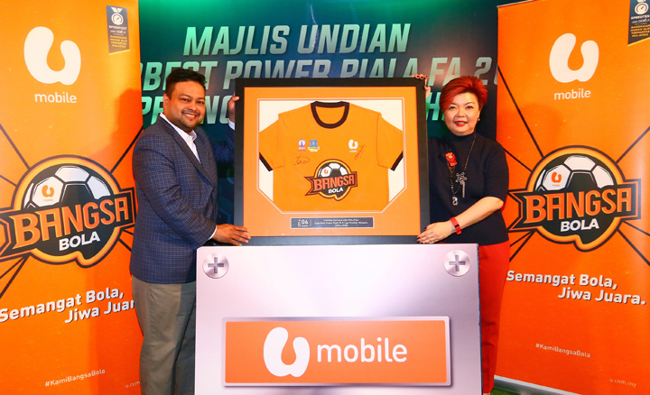 (L – R): Football Malaysia LLP Chief Executive Officer Kevin Ramalingam and U Mobile SdnBhd Chief Marketing Officer Jasmine Lee at the signing ceremony holding up the signed jersey commemorating the partnership between U Mobile and FMLLP as co-sponsors for Superbest Power Piala FA and Liga Premier Malaysia